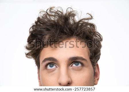 Crop image of a handsome young man with curly hair looking up at copyspace - stock photo