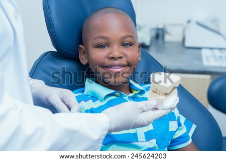 Cropped dentist showing young boy prosthesis teeth in the dentists chair - stock photo