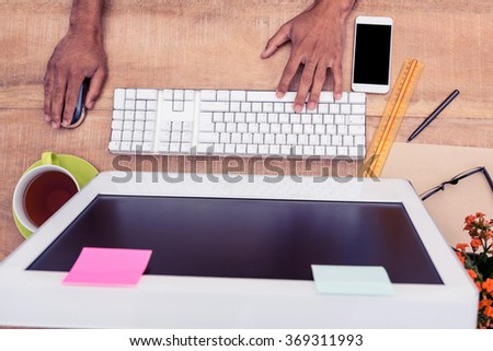 Cropped hand businessman working on computer at table in office - stock photo