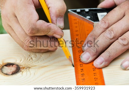 Cropped hand of a carpenter taking measurement of a wooden plank  - stock photo