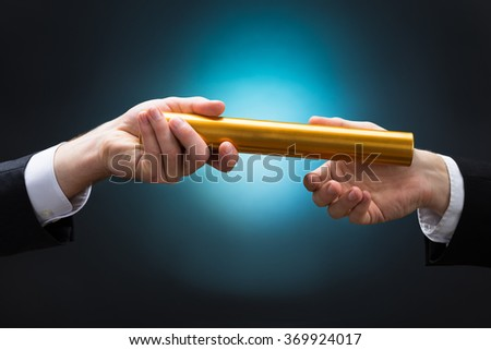 Cropped hand of businessman passing golden relay baton to colleague against blue background - stock photo