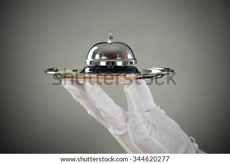 Cropped hand of waiter holding service bell in tray against gray background - stock photo