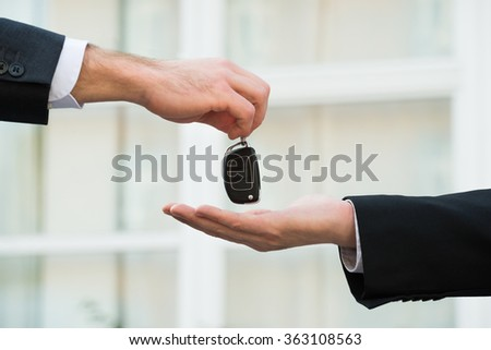 Cropped hands of car dealer giving keys to businessman outdoors - stock photo