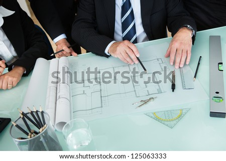 Cropped high angle view of the hands of a group of architects discussing a blueprint or architectural drawing laid out on a tabletop - stock photo