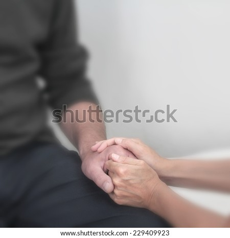Cropped image focusing on therapist holding client's hand offering comfort with a soft blur effect on everything except the hands.  - stock photo