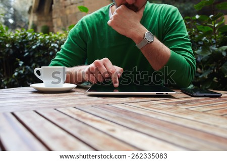 Cropped image male freelancer sitting at the table with cup of coffee, digital tablet and smart phone, man's hands typing message on touch screen tablet while sitting on balcony terrace - stock photo