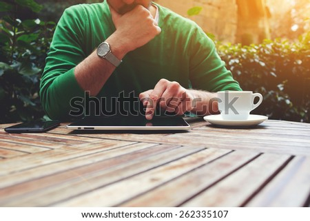 Cropped image male freelancer sitting at the table with cup of coffee, digital tablet and smart phone, man's hands typing message on touch screen tablet while sitting on balcony terrace, flare sun - stock photo