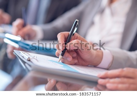 Cropped image of a businessman being at the conference and making notes on the foreground  - stock photo