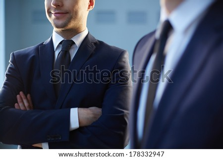 Cropped image of a confident businessman standing near his colleague on the foreground  - stock photo