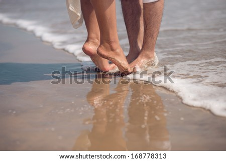 Cropped image of a couple having romantic date on a sandy beach  - stock photo
