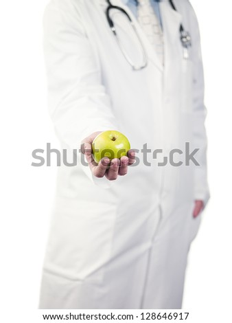 Cropped image of a doctor holding green apple over white background, Model: Derek Gerhardt - stock photo