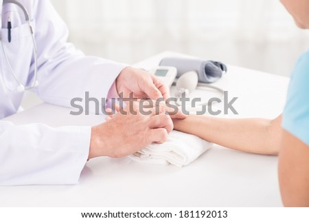 Cropped image of a doctor measuring patient's pulse on the foreground  - stock photo