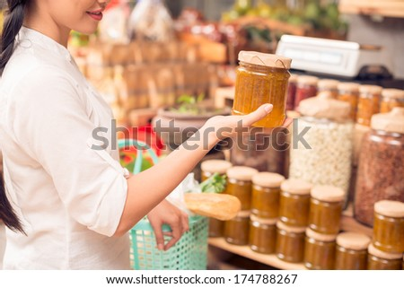 Cropped image of a female customer buying a container on homemade tangerine jam in the store  - stock photo