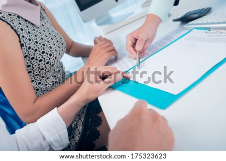 Cropped image of a financial consultant showing the place of a signature to the clients on the foreground  - stock photo