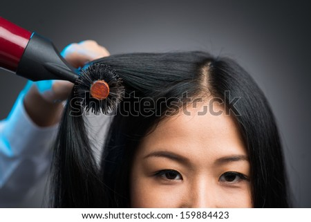 Cropped image of a hairstylist drying the hair of the customer at the beauty salon isolated on grey - stock photo