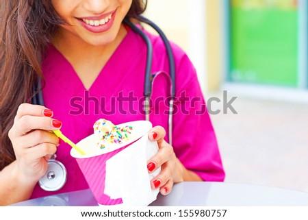 Cropped image of a happy young female doctor having frozen yogurt. Horizontal shot. - stock photo