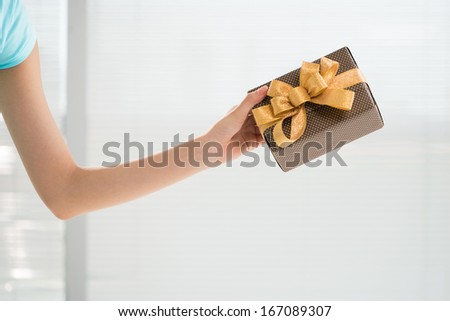 Cropped image of a human hand holding a giftbox  - stock photo