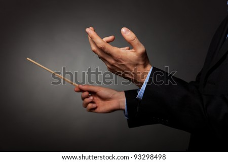 Cropped image of a male music conductor directing with his baton in concert - stock photo