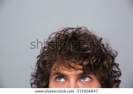 Cropped image of a man with curly hair looking up at copyspace over gray background - stock photo
