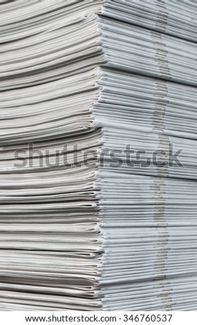 Cropped image of a pile of freshly printed newspapers hot off the press. - stock photo