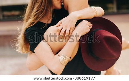 Cropped image of a portrait of stylish couple. There are fashion details bracelet and a hat - stock photo