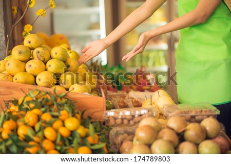 Cropped image of a saleswoman suggesting to buy a great variety of fresh fruit  - stock photo