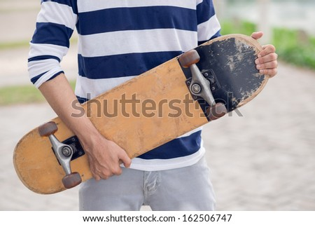Cropped image of a sporty young man holding a skateboard in hands  - stock photo