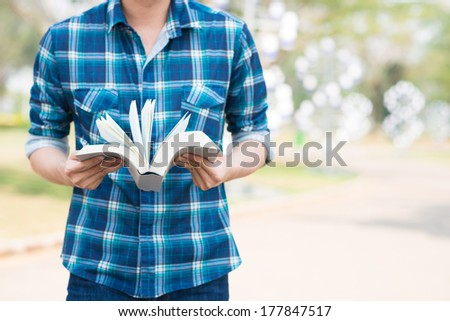 Cropped image of a student with an open book in hands - stock photo