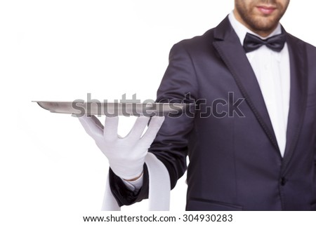 Cropped image of a waiter holding an empty silver tray, isolated on white background - stock photo