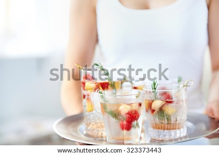 Cropped image of a woman holding a tray of cocktails, mocktails, refreshing drinks with garnish, raspberries and sliced apple in them - stock photo