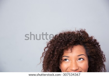 Cropped image of african woman looking up at copyspace over gray background - stock photo