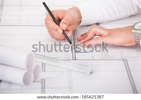 Cropped image of architect's hands working on blueprint design in office - stock photo