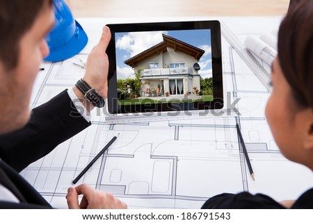 Cropped image of architects with digital tablet looking at photo of the house  - stock photo