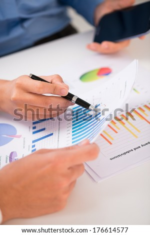 Cropped image of business colleagues discussing financial aspects of the company on the foreground  - stock photo