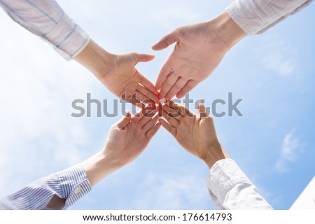 Cropped image of business colleagues holding hands together in the sign of cooperation over sky - stock photo