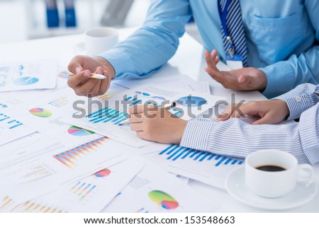 Cropped image of business people discussing business strategy on the foreground - stock photo