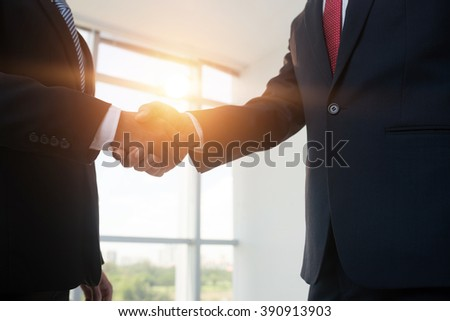 Cropped image of business people shaking hands, backlit - stock photo