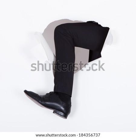 Cropped image of businessman breaking through white paper wall - stock photo