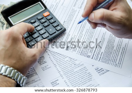 Cropped image of  Businessman calculating and checking tax - stock photo