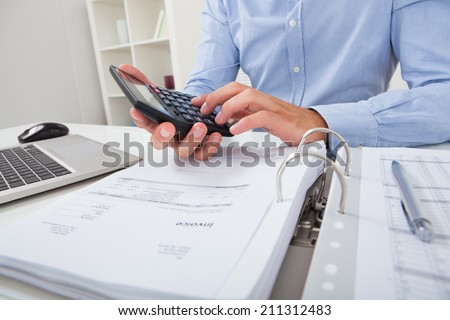 Cropped image of businessman calculating tax at desk in office - stock photo