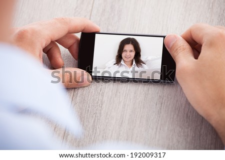 Cropped image of businessman chatting with female colleague through smartphone at office table - stock photo