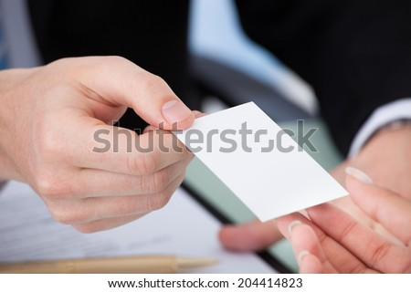 Cropped image of businessman giving visiting card to woman in office - stock photo