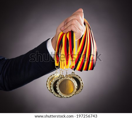 Cropped image of businessman holding gold medals against black background - stock photo