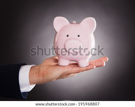 Cropped image of businessman holding piggybank over black background - stock photo