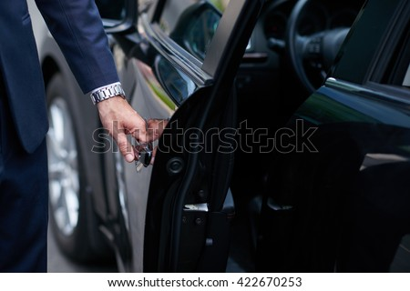 Cropped image of businessman opening door on his car - stock photo