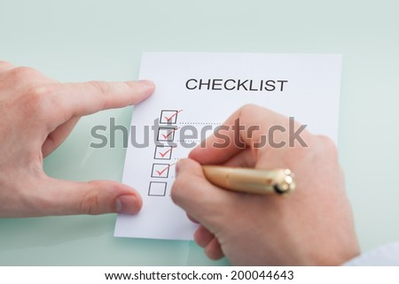 Cropped image of businessman preparing checklist at office desk - stock photo