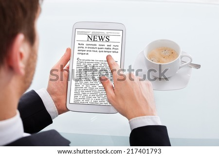 Cropped image of businessman reading news on digital tablet at desk in office - stock photo