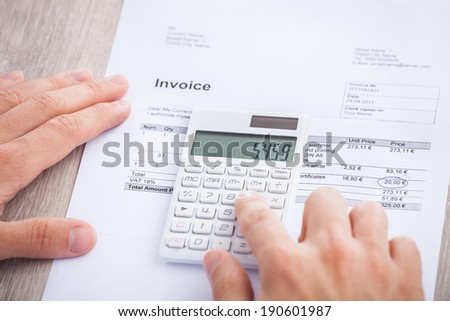 Cropped image of businessman's hands calculating invoice at desk - stock photo