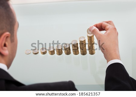Cropped image of businessman stacking coins in increasing order at office desk - stock photo