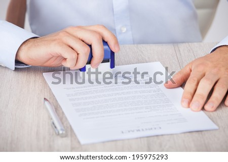 Cropped image of businessman stamping contract paper at desk in office - stock photo